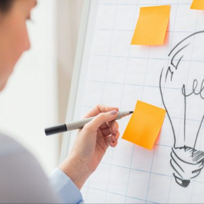 business, people, idea, startup and education concept - close up of hand with marker drawing light bulb or writing to sticker on flip chart at office